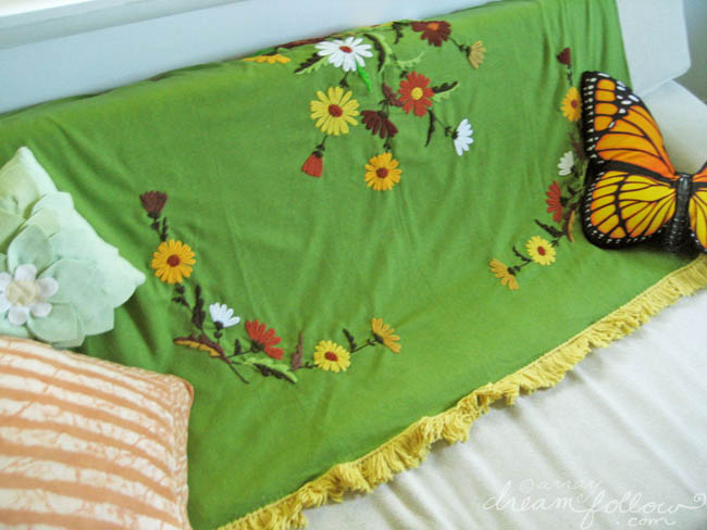 Vintage green crewel floral blanket on couch.
