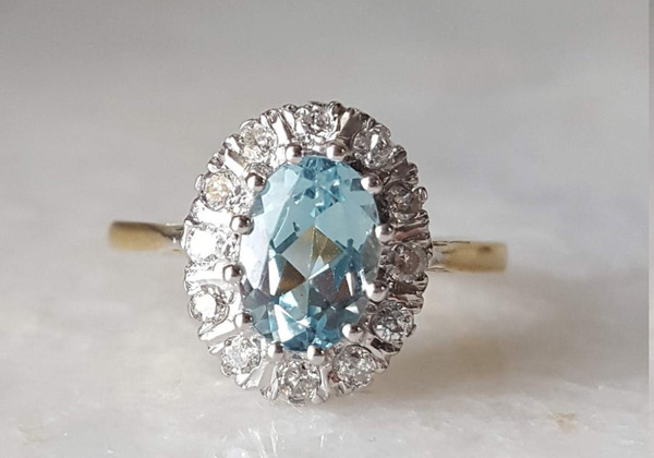 A vintage aquamarine and diamond halo ring offered by LovelyLittleRingsEtc