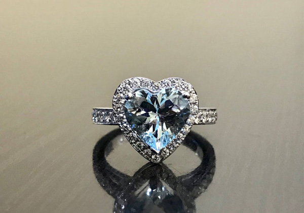 A platinum, diamond, and aquamarine heart shaped ring offered by DeKaraDesigns