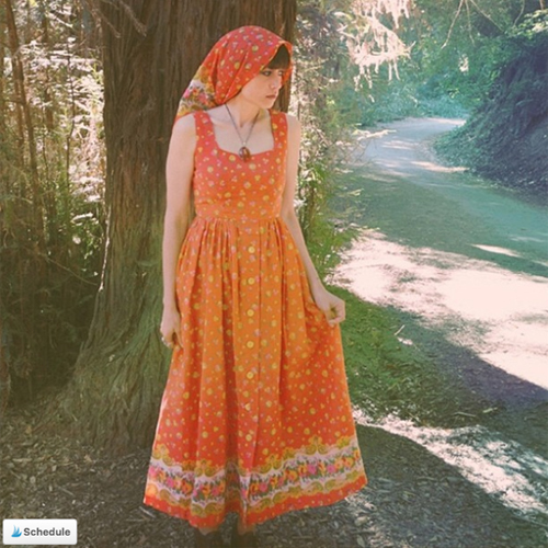Woman wearing a long vintage boho gown and head scarf in Oakland's Redwood Forest.