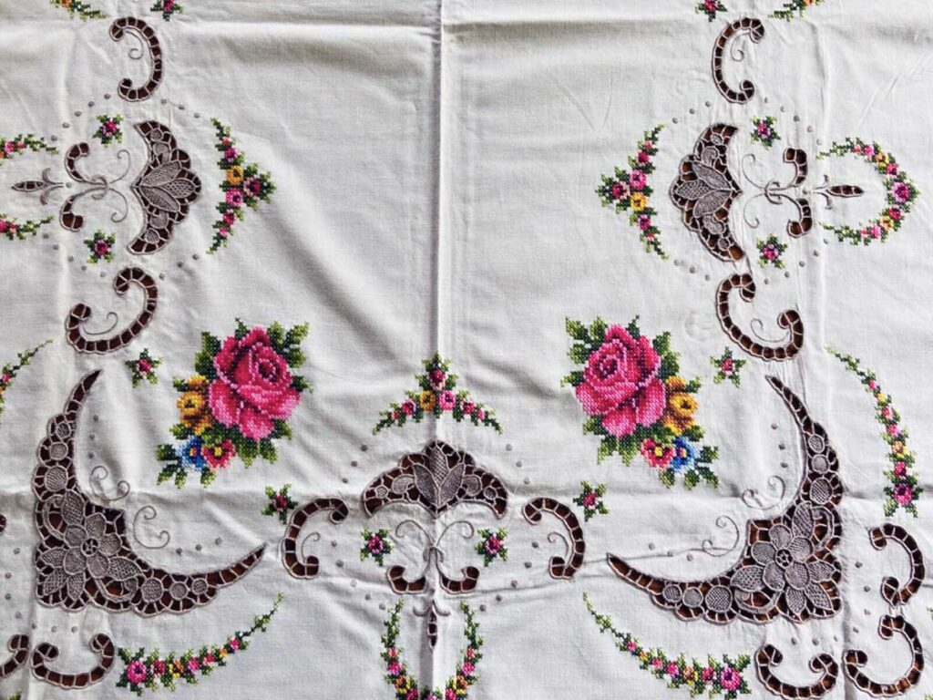Large vintage tablecloth with embroidered pink roses and floral lace.